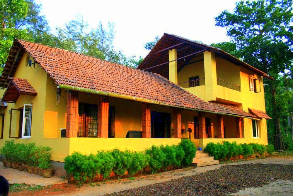 a Karnataka style home painted yellow and red with plants on the verandah