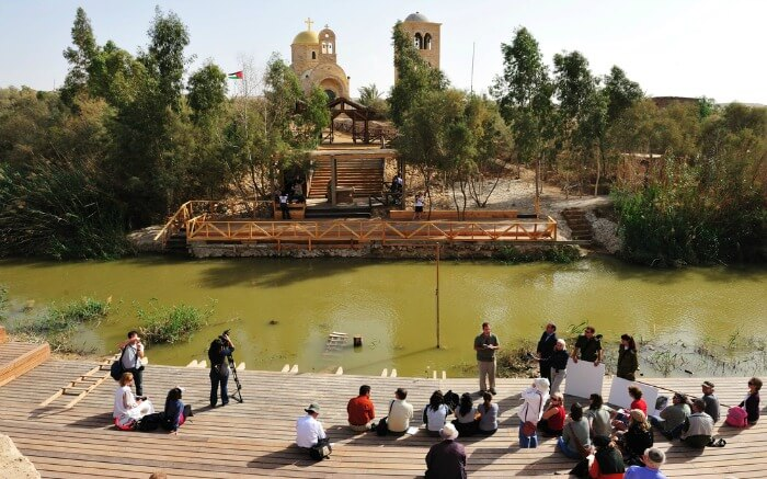 Pilgrims at riverbank in Qasr el Yahud in Jordan