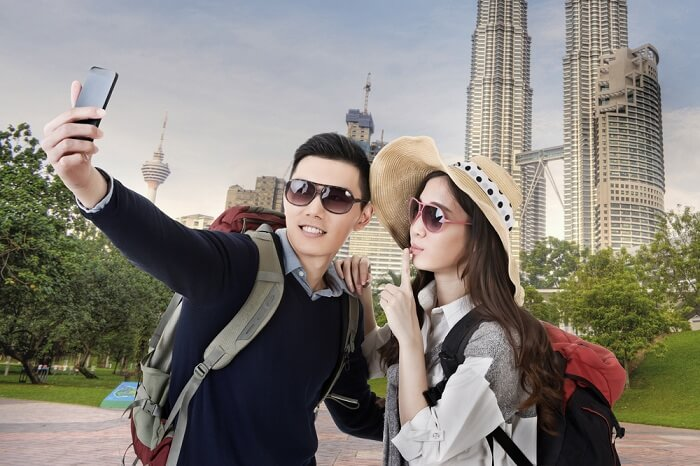 Asian couple travel and take selfie in Kuala Lumpur