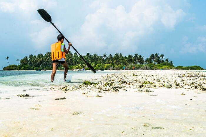 A child on Kalpeni beach with kayak paddle