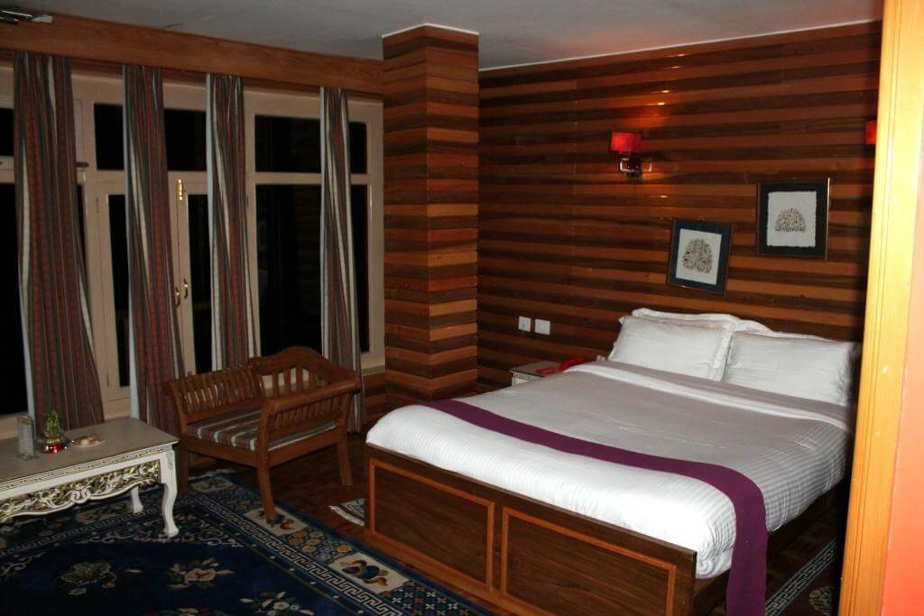 a room with wooden decor and a big bed and sofa