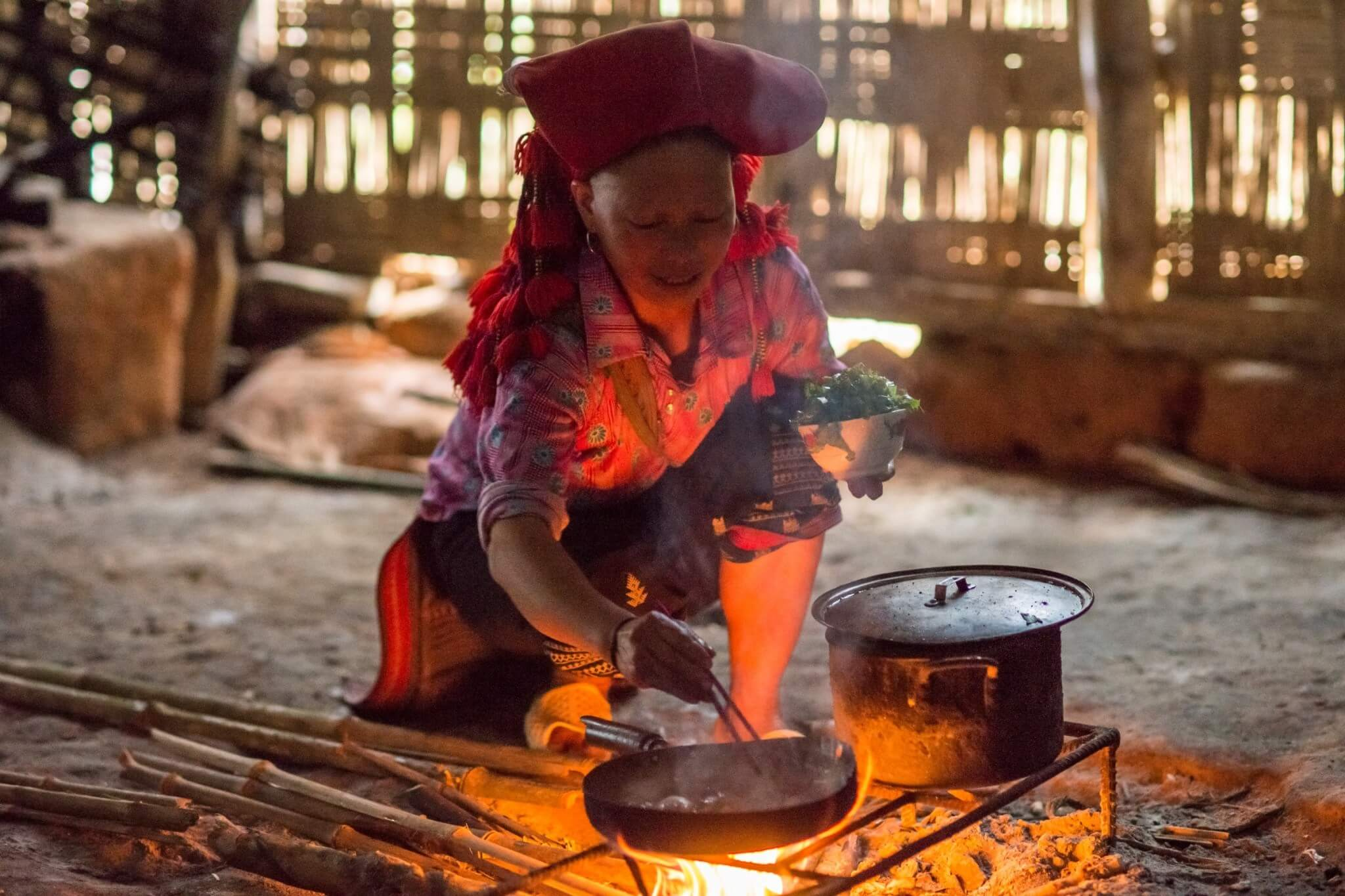 an old lady cooking food on mud stove