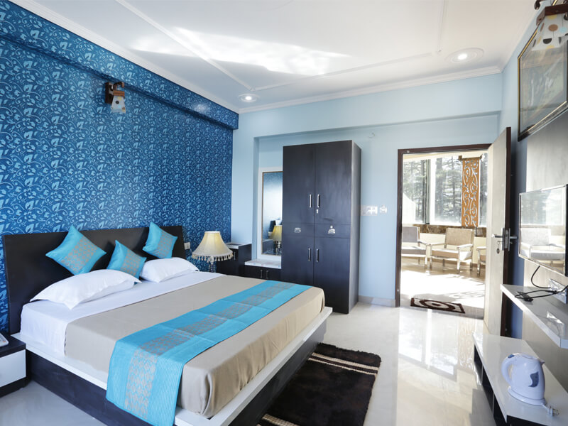 A stylish hotel room with a king size bed and wooden almirah