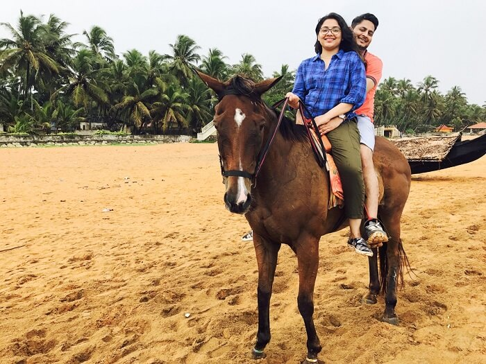aarti and revan riding horse on beach in kovalam, kerala