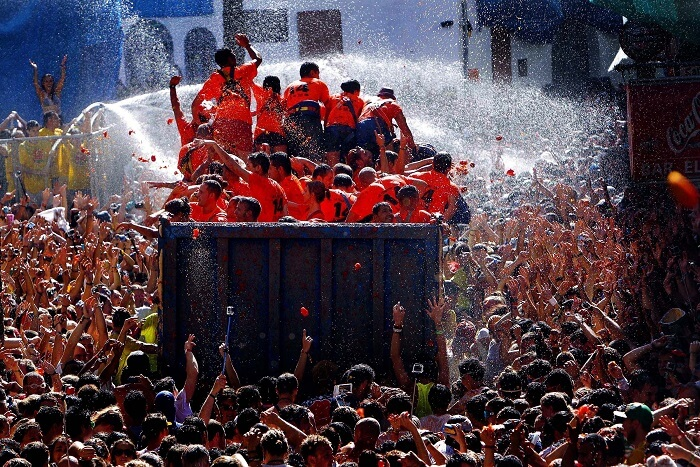 lorries dispersing water to clean participants in tomatina