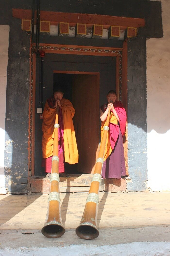 monks with trumpets in bhutan