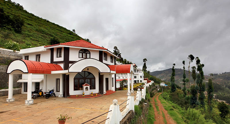 a red and white resort in the foggy hills of Kodaikanal