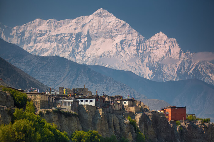 Tibetan style home and snow clad mountains during Upper Mustang Trek