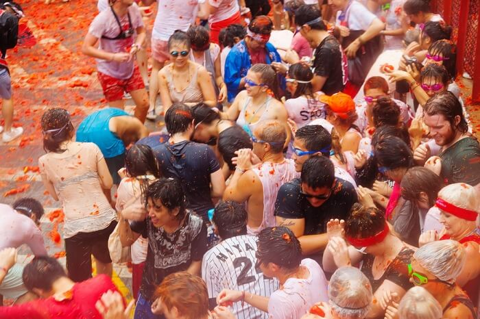 people indulging in tomato fight at tomatina