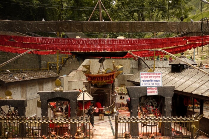 Entrance of an ancient temple decorated with red flags and statues
