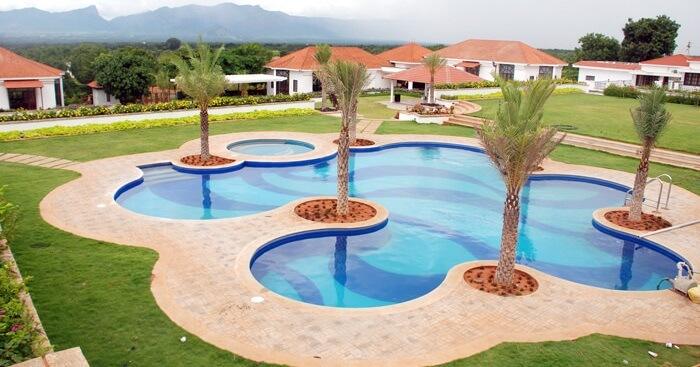 A snap of the swimming pool and the surrounding cottages at the Bungalow Club Resort in Coimbatore