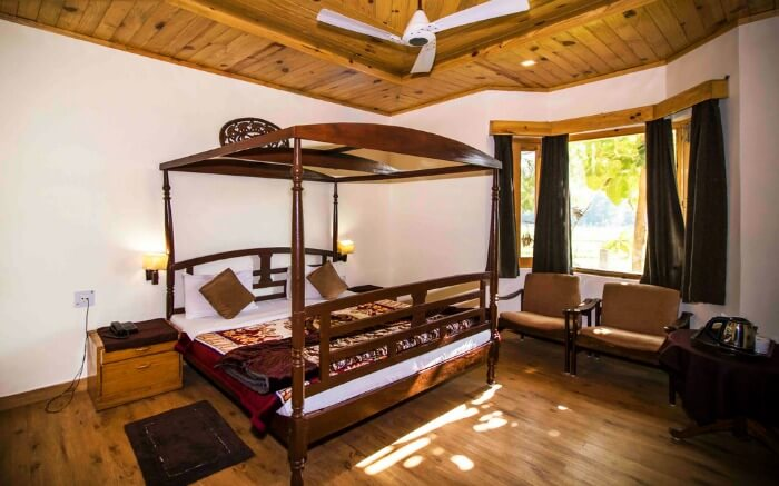 hotel room with wooden bed, sofas, and a glass window