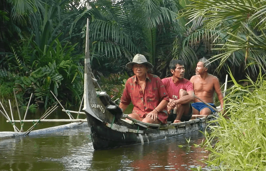 three men rowing a boat in water