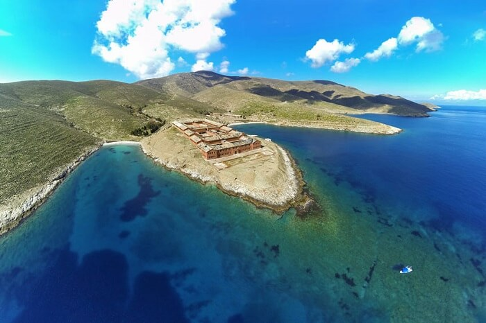 An aerial shot of the prison on the island of Gyaros in Greece along with the azure waters surrounding it