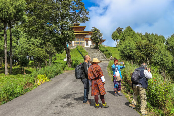 foreigners with a Bhutanese man outside a temple