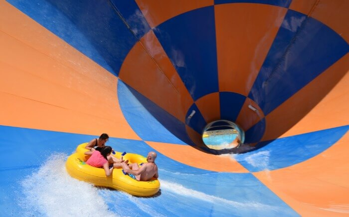 three people enjoying in a water swing in Wet n Wild theme park