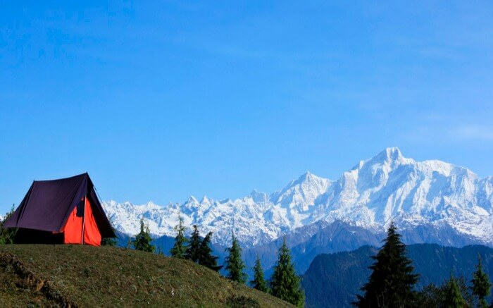 A camp perched at the top overlooking snow capped mountains in Uttarakha