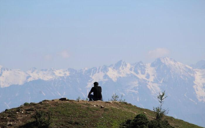 A traveler sitting on the edge of a cliff at Hatu Peak Narkanda