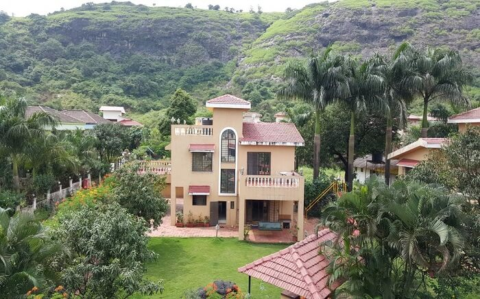 A view of Aashiyana Villa in Lonavala surrounded by hills and plantation
