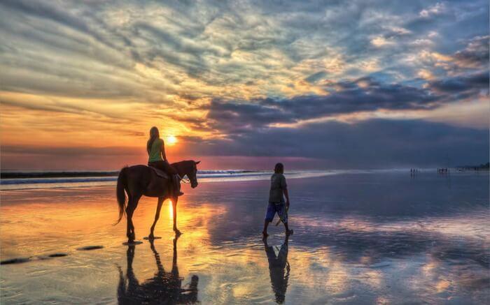 A woman riding a horse by the ocean near Canggu Beach