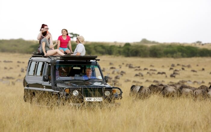 Group of tourists enjoying in an open roof jeep during a safari in Kenya