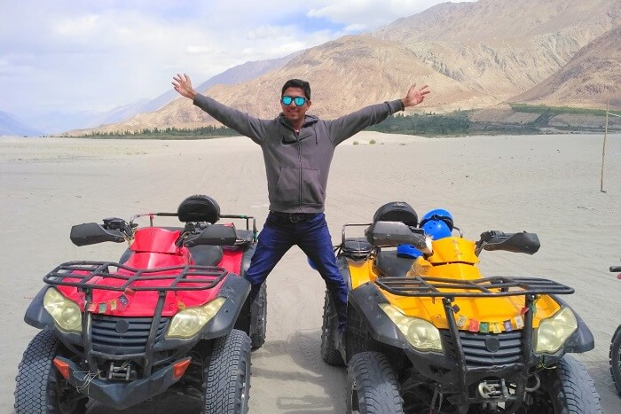 ninad posing on two atv bikes