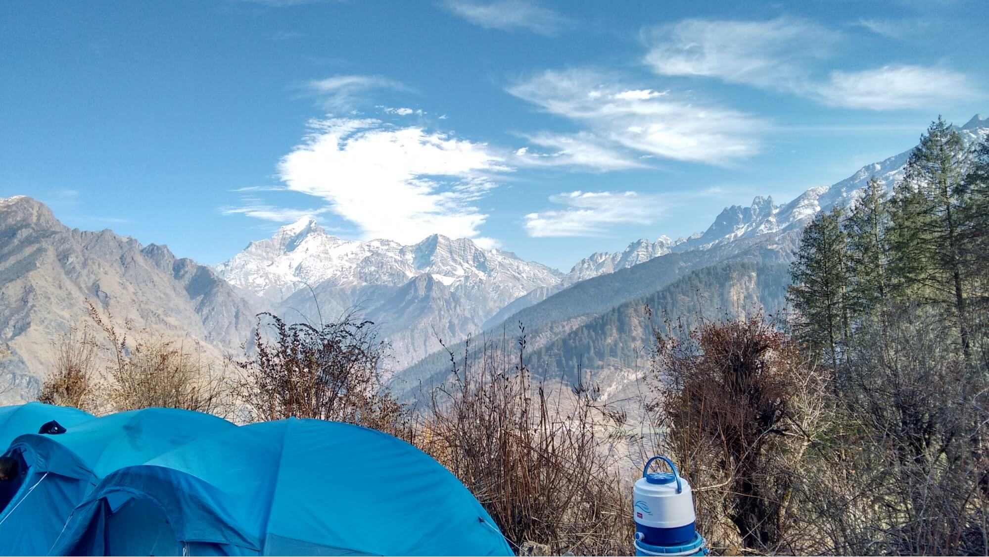 a blue tent pitched in the mountains