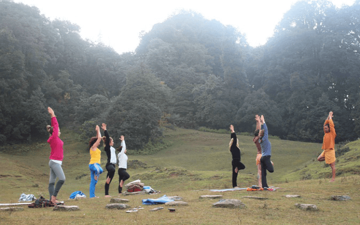 Travelers taking up yoga in the mountains in Chopta