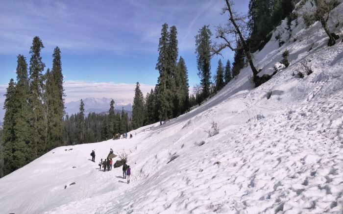Travelers walking snow covered path on their way to Hatu Peak