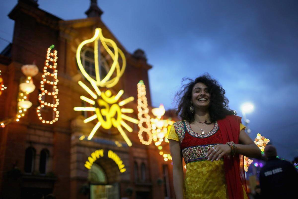 a woman standing outside a temple in London during Diwali