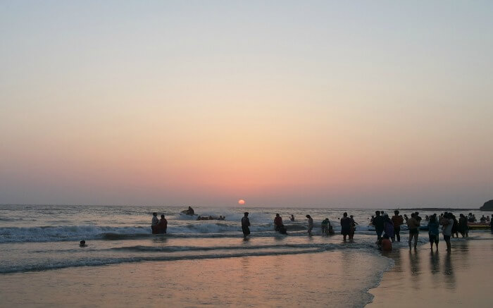 people at a beach during sunset