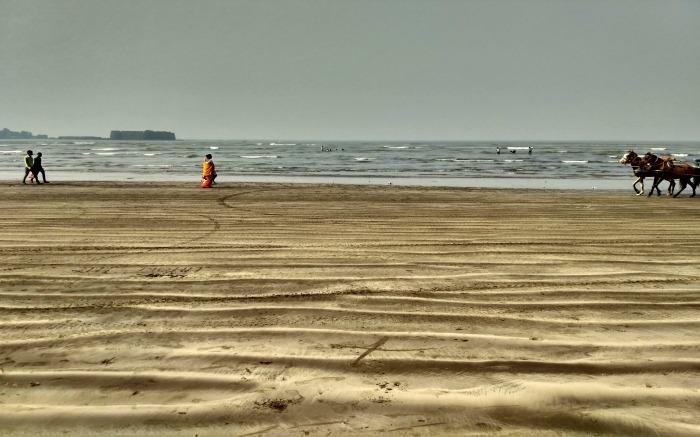 people walking on a sandy beach