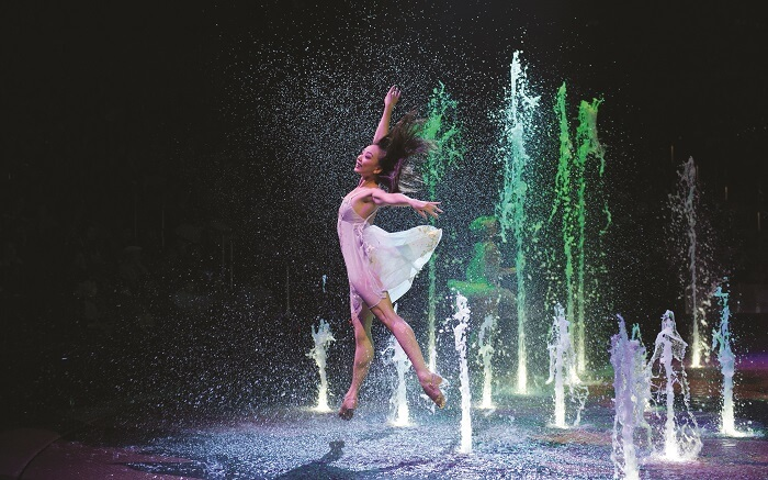A girl dancing as colourful fountains erupt