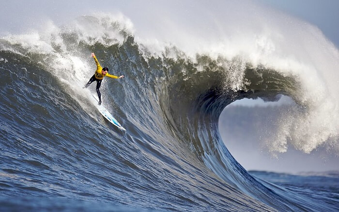 A man wearing yellow clothes surfing in high tides