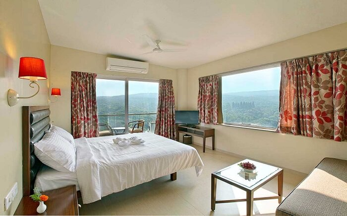 A resort bedroom with glass windows overlooking the mountains