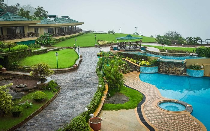 A resort with an outdoor pool and lush lawns
