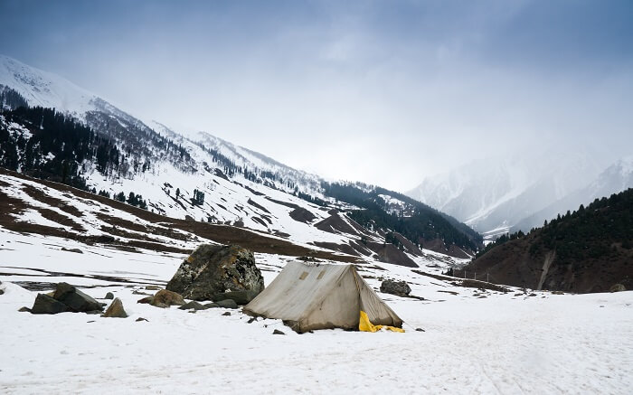 A tent in the middle of snow mountains in Kashmir