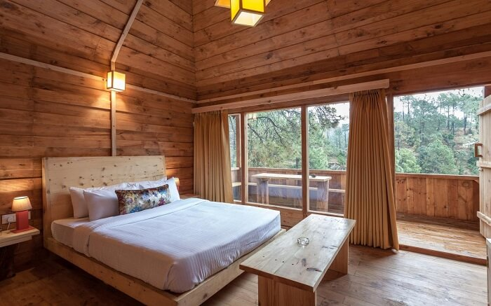 A wooden room with a huge bed and glass windows