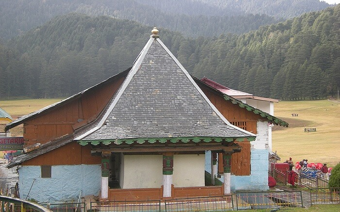 An old temple overlooking thick deodar forest