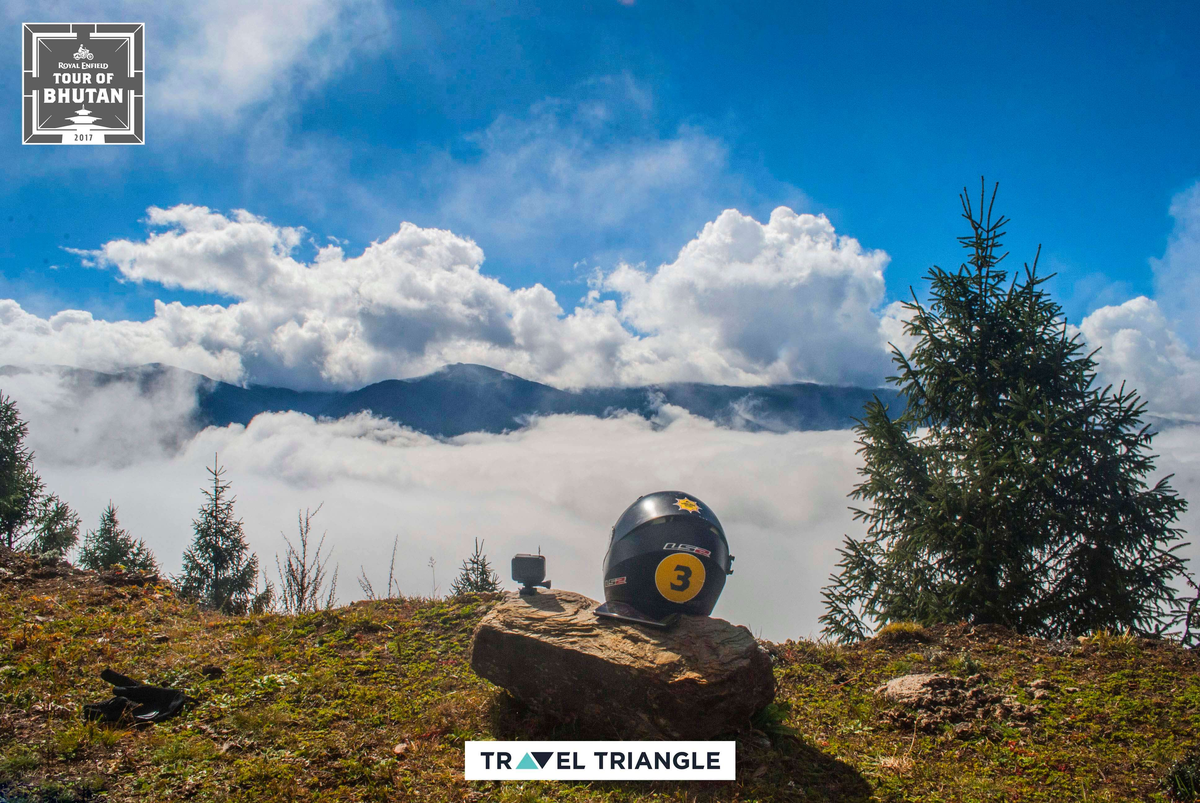 royal enfield india bhutan road trip: a bike helmet and clouds beyond it on the hill