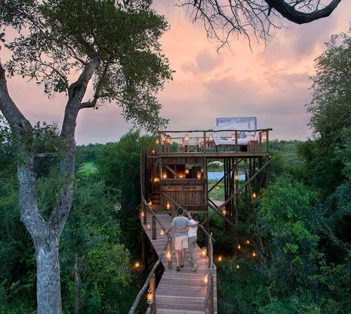 A couple walking the wooden bridge at Tinyeleti Treehouse in Lion Sands in Africa