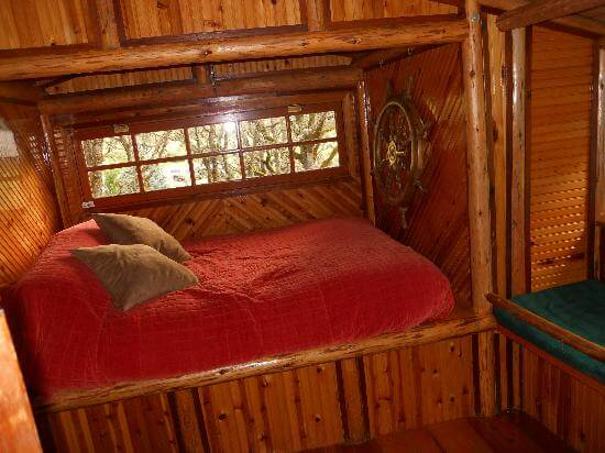 Well laid bed and beautiful interiors of Out N' About Treehouse Treesort in Oregon