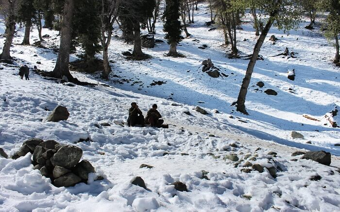 People sitting in the midst of the valley in Sonamarg covered in snow