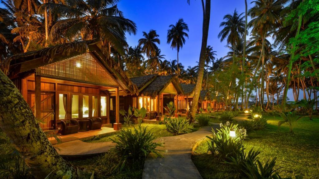 a beautifully lit resort surrounded with palm trees