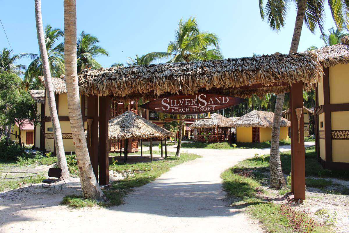 entrance of a beautiful resort with small huts in lawn