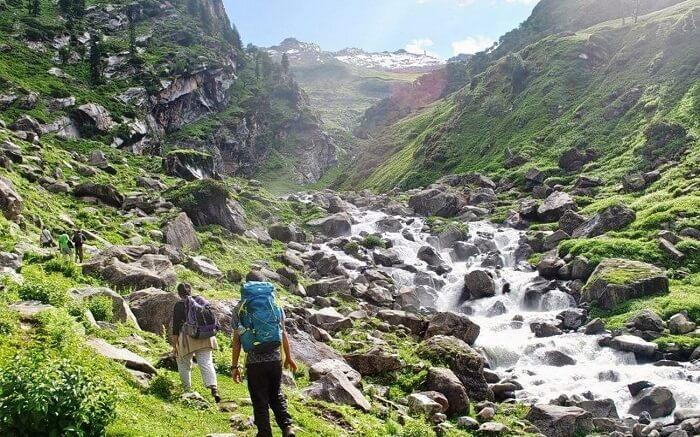 Travelers walking by the stream during Hampta Pass trek in Himachal