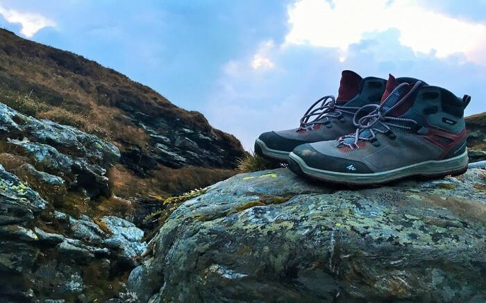 Trekking shoes kept on a boulder overlooking mountains