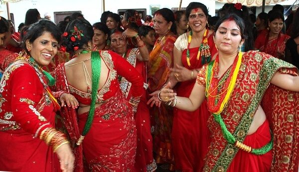 married women wearing red sarees and dancing