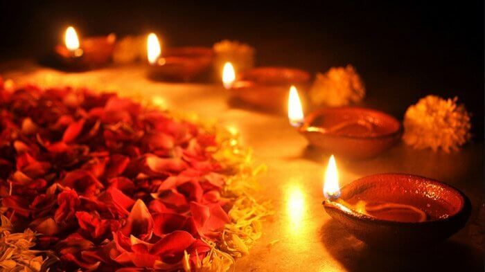 lit earthen diya and flowers