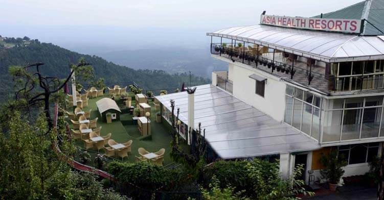 a resort with a huge lawn in mountains